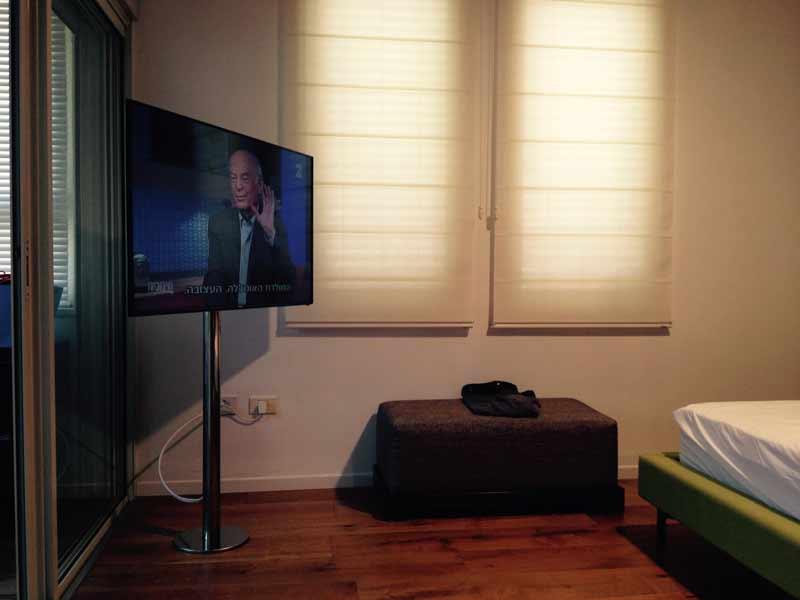 מסך טלוויזיה על עמוד נירוסטה בחדר שינה