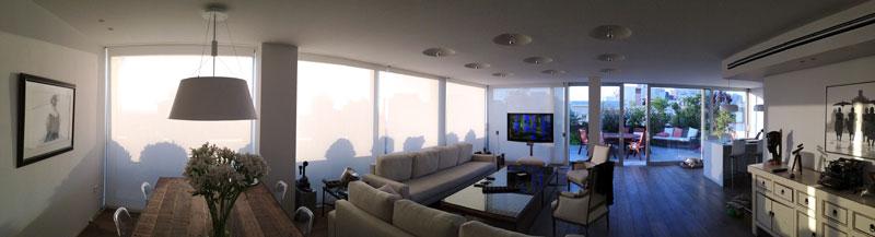 דירה בתל אביב. רמקולים קטנים מעוצבים וטלוויזיה על עמוד