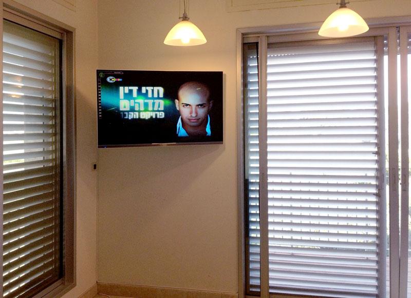 מסך טלוויזיה תלויה בפינה של חדר שינה