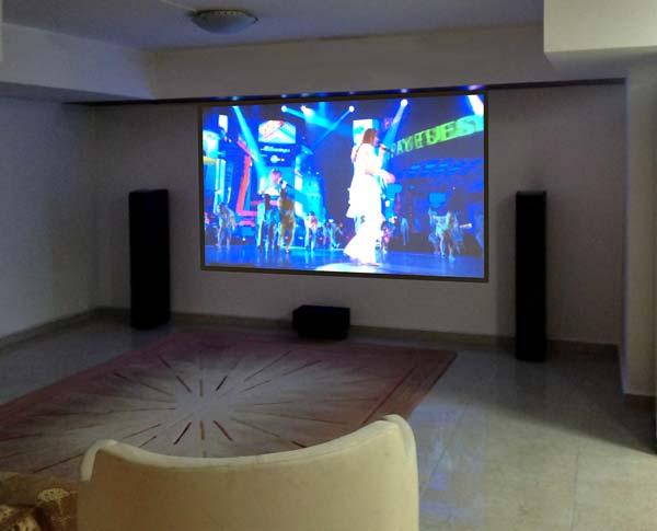 """מערכת קולנוע ביתי בבית פרטי בראשון לציון. רמקולים רצפתיים, מקרן FULL HD, מסך הקרנה של 110"""""""